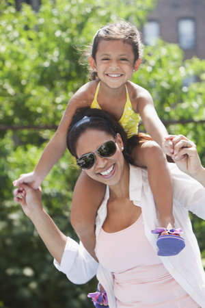 Hispanic mother carrying daughter on shoulders LANG_EVOIMAGES