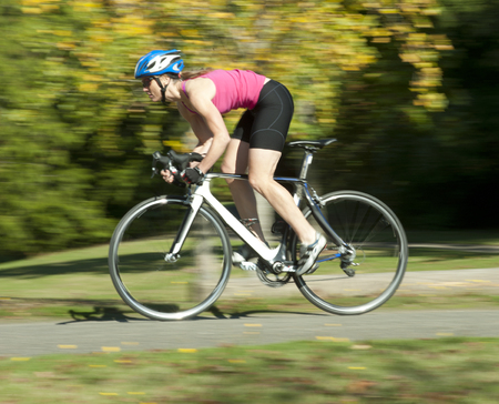 Caucasian woman riding bicycle in park LANG_EVOIMAGES