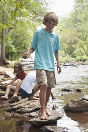 Caucasian children playing near stream
