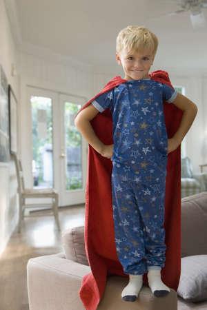 Caucasian boy in superhero costume standing on sofa LANG_EVOIMAGES