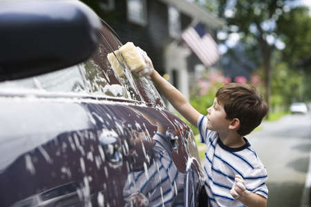 Caucasian boy washing car LANG_EVOIMAGES