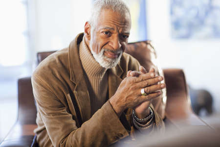 Serious Black man with hands clasped LANG_EVOIMAGES