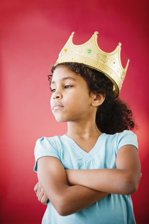 Mixed race girl with arms crossed wearing crown LANG_EVOIMAGES