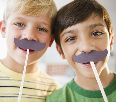 Boys playing with costume mustaches