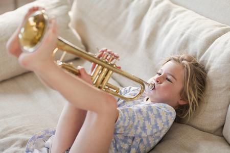 Caucasian girl on sofa playing trumpet