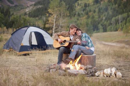 Caucasian man playing guitar for wife near campfire