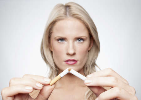 Caucasian woman breaking cigarette LANG_EVOIMAGES