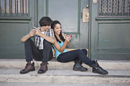Couple using cell phones on front stoop