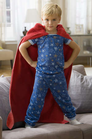 Caucasian boy in superhero costume standing on sofa LANG_EVOIMAGES