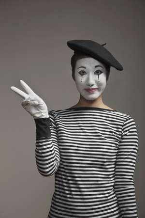 Woman in mime costume making peace sign