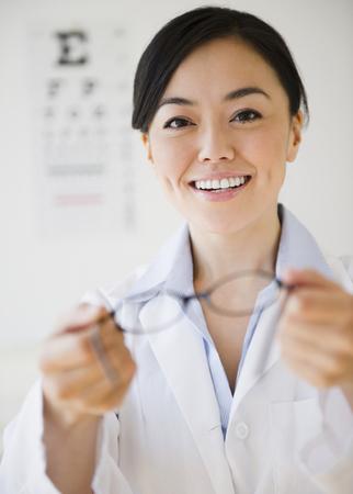 Japanese optometrist holding eyeglasses LANG_EVOIMAGES