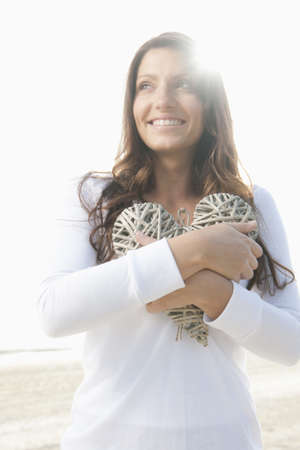 Hispanic woman holding large,woven heart LANG_EVOIMAGES