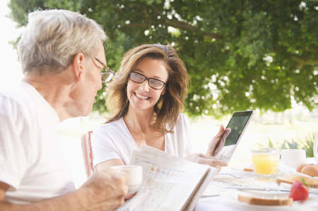 Caucasian woman showing husband digital tablet at breakfast LANG_EVOIMAGES