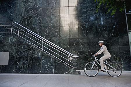 Businesswoman riding bicycle on sidewalk