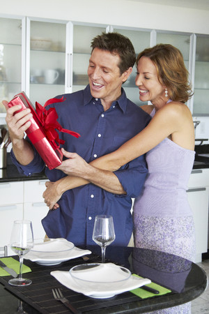 Caucasian woman giving husband a gift LANG_EVOIMAGES