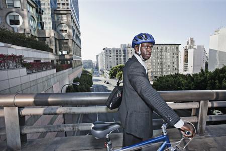 Businessman pushing bicycle over urban bridge LANG_EVOIMAGES
