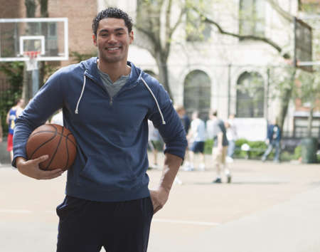 Mixed race man holding basketball on basketball court LANG_EVOIMAGES