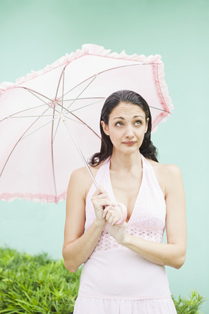 Caucasian woman holding parasol LANG_EVOIMAGES