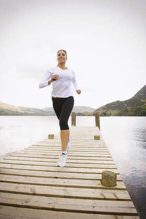 Hispanic woman running on pier