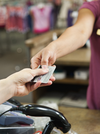Woman handing over credit card in store