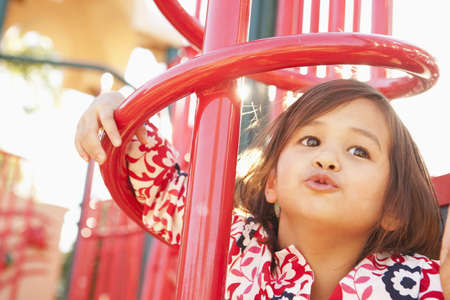 Mixed race girl playing in playground
