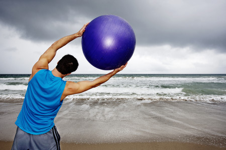 Young man holding exercise ball on beach