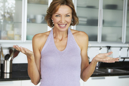Smiling Caucasian woman standing in kitchen LANG_EVOIMAGES