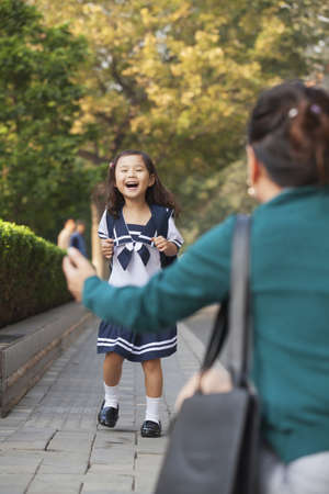 Chinese mother greeting daughter in school uniform