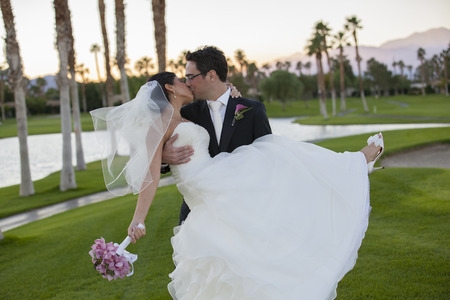 Newlywed couple kissing on golf course LANG_EVOIMAGES