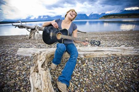 Caucasian woman playing guitar near lake LANG_EVOIMAGES