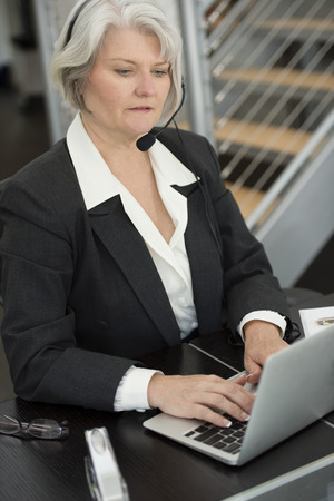 Smiling Businesswoman in headset typing on laptop LANG_EVOIMAGES