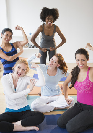Women showing muscles on yoga mats LANG_EVOIMAGES