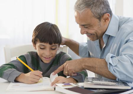 Hispanic grandfather helping grandson with homework
