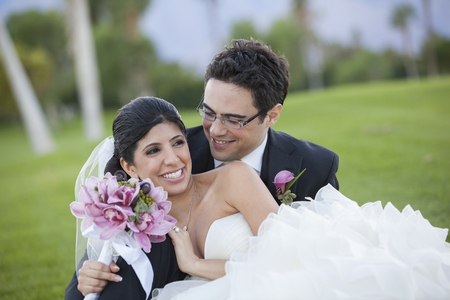 Newlywed couple hugging on golf course
