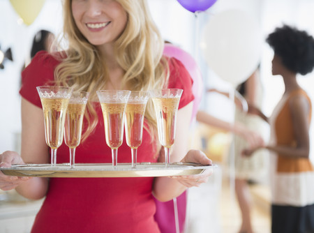 Smiling woman carrying tray of champagne LANG_EVOIMAGES