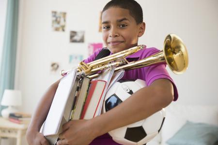 Hispanic boy carrying trumpet,books and soccer ball