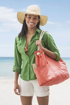 Black woman carrying tote bag on beach