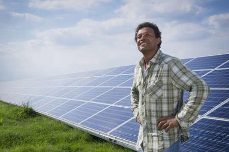 Mixed race man standing near solar panels LANG_EVOIMAGES