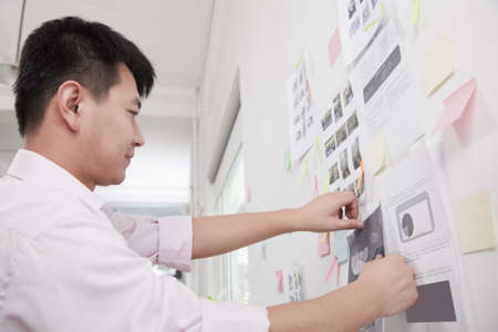 Chinese businessman making display in office
