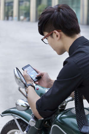 Chinese businessman using cell phone on motorcycle
