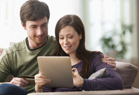 Caucasian couple using tablet computer on sofa LANG_EVOIMAGES