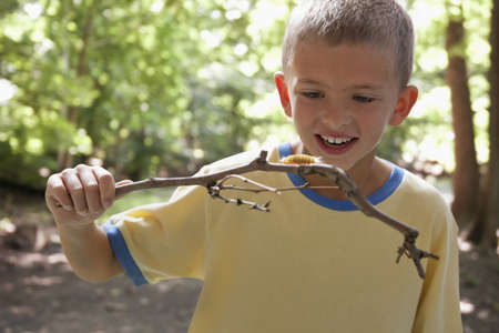 Boy examining caterpillar outdoors