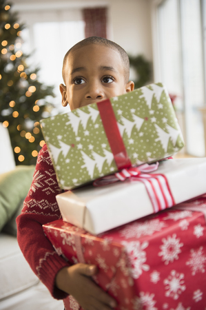 African American boy carrying Christmas presents