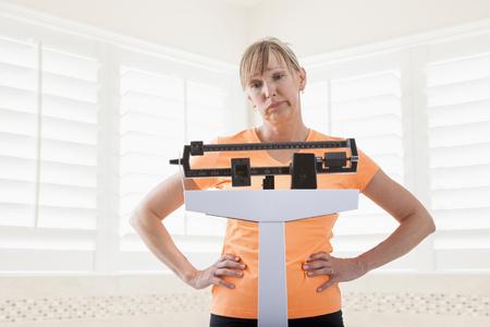 Caucasian woman weighing herself
