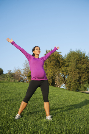 Pregnant Hispanic woman stretching outdoors