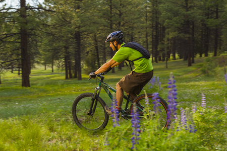 Hispanic man riding mountain bike in meadow
