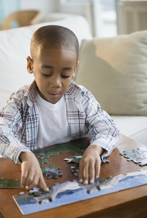 African American boy playing with jigsaw puzzle LANG_EVOIMAGES