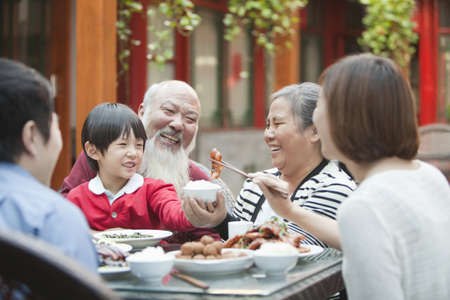 Chinese family eating at table outdoors