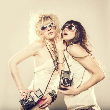 Mujeres caucásicas posando con cámaras