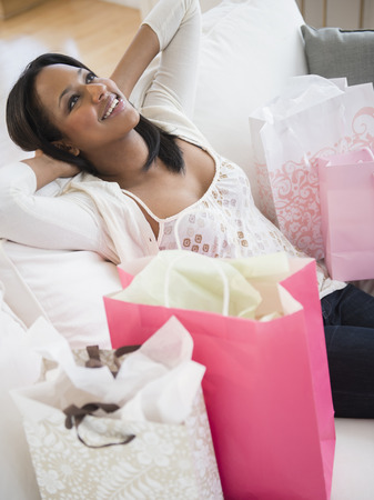 African American woman with shopping bags on sofa LANG_EVOIMAGES